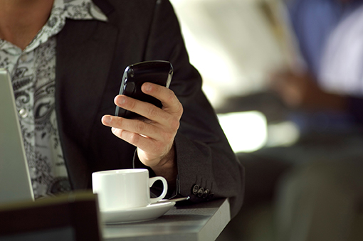 Person with coffee looking at smartphone